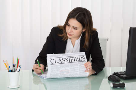 job: Young Businesswoman Highlighting Advertisement On Newspaper In Office