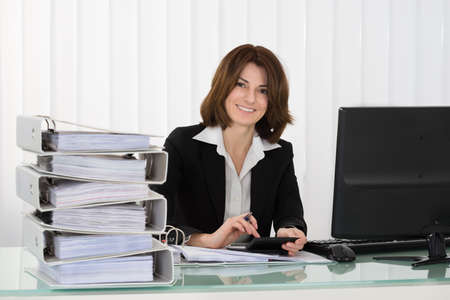 ring binder: Young Happy Businesswoman Working With Documents In Office