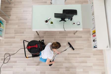 personal de limpieza: Suelo de madera Mujer de limpieza Portero joven con el aspirador