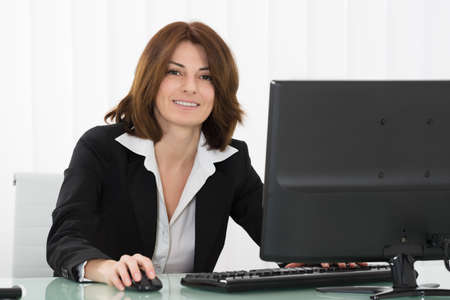 desktop computer: Happy Young Businesswoman Working On Computer At Office Stock Photo