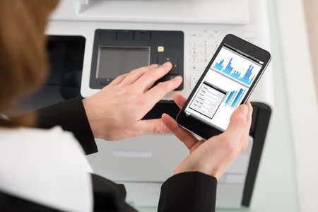 copier: Close-up Of Businesswoman Giving Print Command On Smart Phone