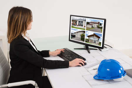 architect: Young Female Architect Looking At Designs Of House On Computer In Office