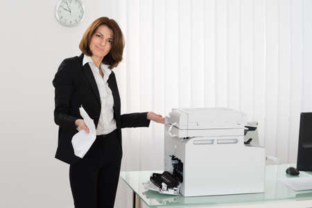 office manager: Unhappy Businesswoman Holding Crumpled Paper Standing Near Photocopy Machine