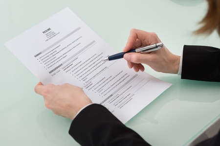 cv: Close-up Photo Of Person Hand Holding Resume Stock Photo