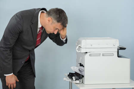 Irritated Mature Businessman Looking At Printer Machine At Office