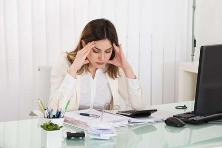 upset: Young Depressed Businesswoman Calculating Invoice In Office Stock Photo