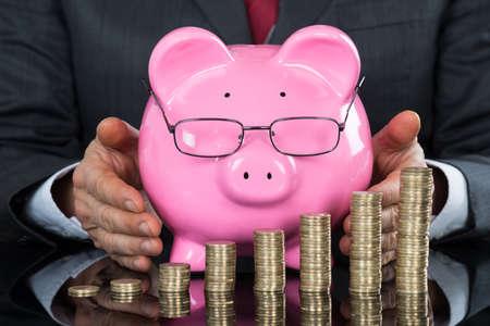 sheltering: Close-up Of Businessman Hand Sheltering Piggybank And Coins At Desk