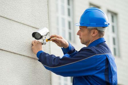 seguridad en el trabajo: Hombre maduro Técnico Instalación de la cámara en la pared con destornillador