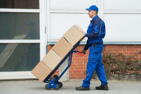 carretilla de mano: Madura feliz Hombre de salida que lleva cuadros sobre un carro de mano en la calle Foto de archivo