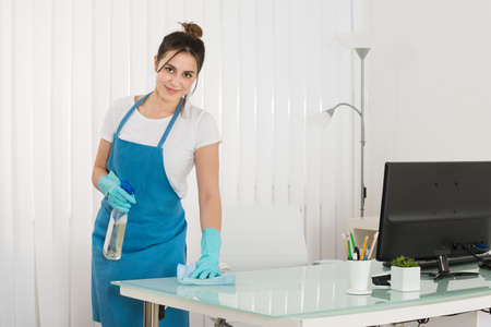 wipe: Happy Young Female Janitor Using Spray To Wipe Desk