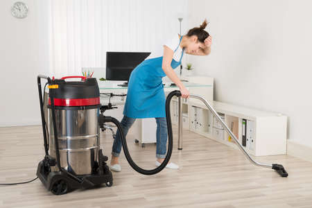 cleaning woman: Tired Young Female Janitor Cleaning Floor With Vacuum Cleaner Stock Photo