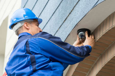 video wall: Close-up Of Mature Male Technician Installing Camera