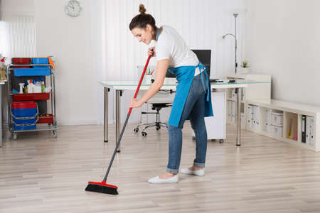 Young Female Janitor Sweeping Floor With Broom Banco de Imagens