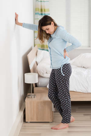 back ache: Woman Suffering From Back Ache Standing Against Wall Stock Photo