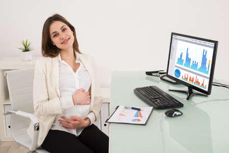 mujer sentada: Embarazada ordenador joven empresaria de trabajo en el despacho Foto de archivo