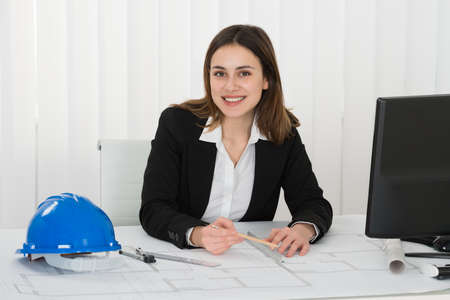 female architect: Young Happy Female Architect Drawing Blueprint In The Office