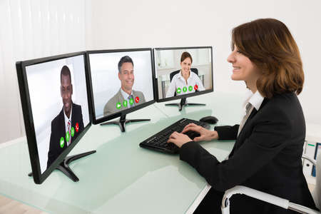 conferencing: Businesswoman Video Conferencing On Desk With Multiple Computers