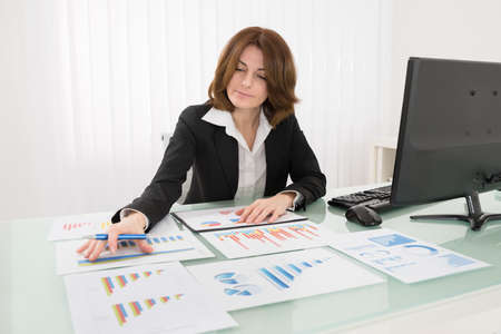 business chart: Businesswoman Analyzing Graph On Desk In Office Stock Photo