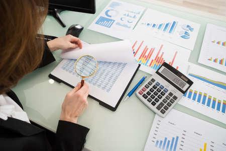 Businesswoman Regardant Rapport financier Grâce Loupe