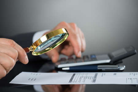 Close-up Of Businessman Hand Inspecting Invoice With Magnifying Glass And Calculator At Desk Фото со стока