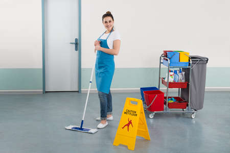 janitor: Female Janitor Mopping Corridor With Caution Sign