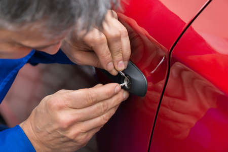 Primer De La Persona mano que sostiene el LockPicker para abrir la puerta del coche Foto de archivo