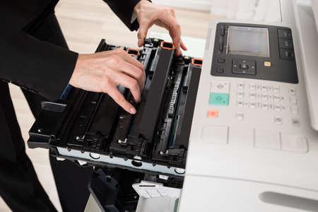 copy machine: Close-up Of Businesswoman Hand Fixing Copy Machine Stock Photo