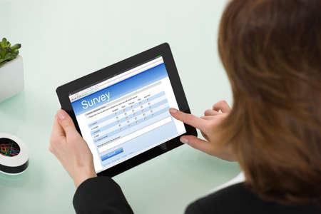 Primer plano de la empresaria rellenado de formularios de encuesta en línea sobre la tableta digital