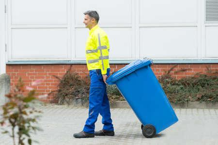 recolector de basura: Trabajador de sexo masculino feliz que recorre con los Cubo de basura en la calle durante el d�a
