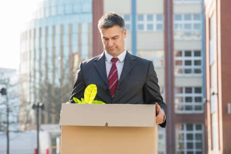 Disappointed Businessman Standing With Cardboard Box Outside Office Stock Photo