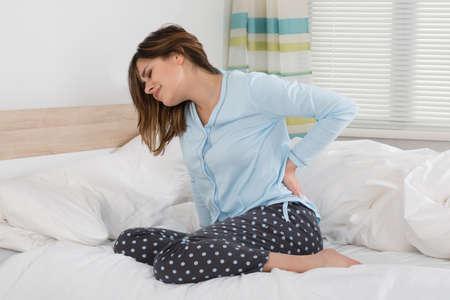 Kobieta cierpi na ból pleców siedzi na łóżku