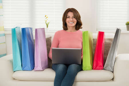 surf shop: Young Happy Woman Sitting On Sofa With Laptop And Shopping Bags