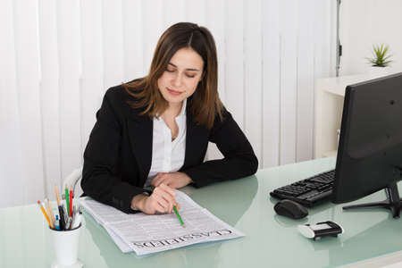 classifieds: Young Businesswoman Reading Classifieds On Newspaper In Office