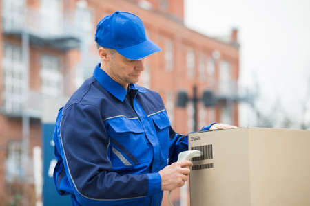 barcode scanner: Delivery Man Standing And Scanning Cardboard Boxes With Barcode Scanner
