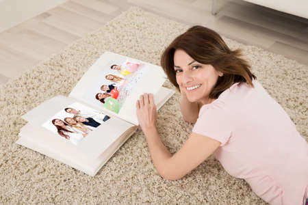 viewing: Happy Young Woman Lying On Carpet With Family Photo Album Stock Photo
