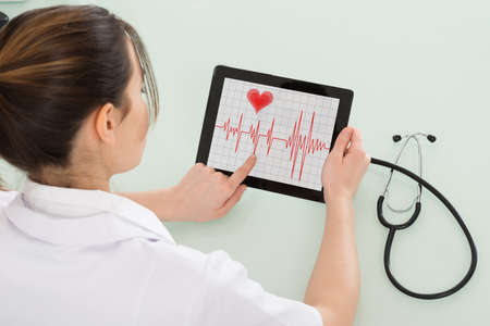 the cardiologist: Close-up Of Young Female Cardiologist Analyzing Heartbeat On Digital Tablet Stock Photo