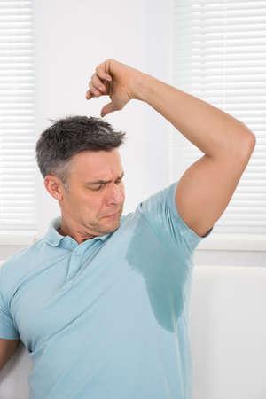 axila: Hombre maduro Avisos su sudor bajo la axila