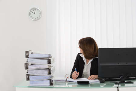 overwork: Young Businesswoman Looking At Clock In Office Stock Photo