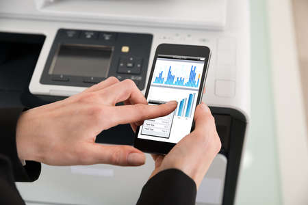 photocopier: Close-up Of Businesswoman Giving Print Command On Smart Phone