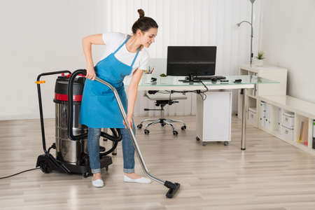 vacuum: Female Janitor Cleaning Floor With Vacuum Cleaner In Office Stock Photo
