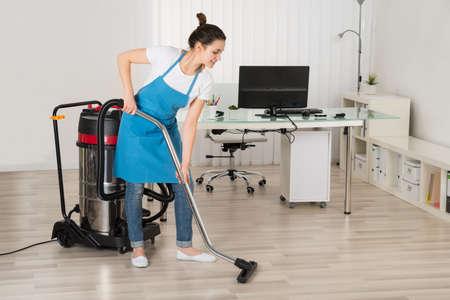 personal de limpieza: Mujer conserje limpieza del piso con la aspiradora en la oficina