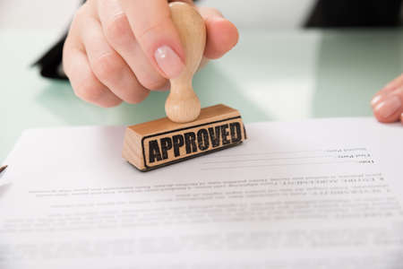 signing authority: Close-up Of Businesswoman Hand Stamping Approved On Contract Paper