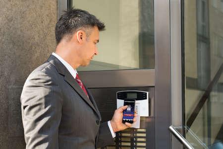 ドアの武装解除のセキュリティ システムのためのスマート フォンを保持している実業家を成熟します。