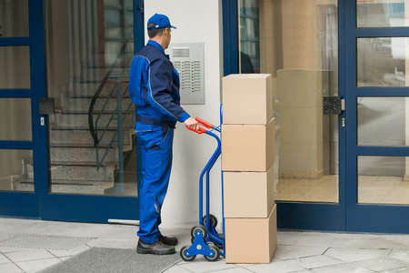 Delivery Man With Trolley Full Of Box Using Security To Enter Building