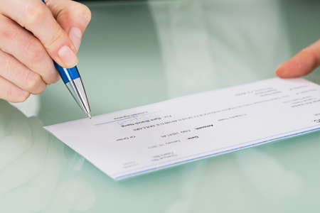 cheque: Close-up Photo Of Businesswoman Hand Signing Cheque