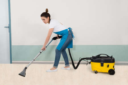 High Angle View Of Young Female Janitor Vacuuming Floor