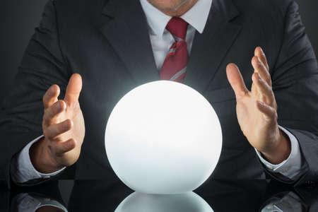 soothsayer: Primer plano del hombre de negocios Mano en la bola de cristal en el escritorio