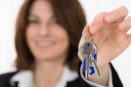 accommodation broker: Happy Young Businesswoman Holding House Key In Office Stock Photo