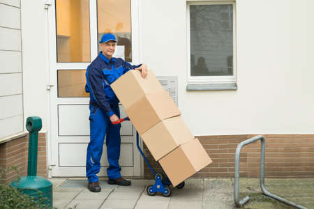 hand truck: Happy Mature Delivery Man Holding Boxes On A Hand Truck