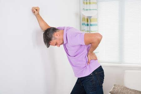 Oudere Mens Die Rugpijn terwijl leunend op een witte muur Thuis